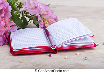 Notebook with bouquet on wooden background
