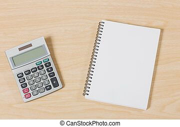 notebook with calculator on wood table