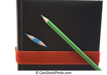 Notebook with coloured pencil on white background