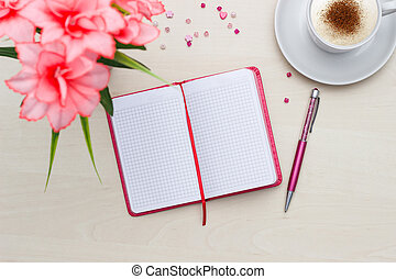Notebook with cup of coffee and flower on wooden