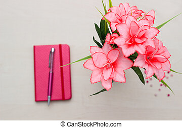 Notebook with flower on wooden