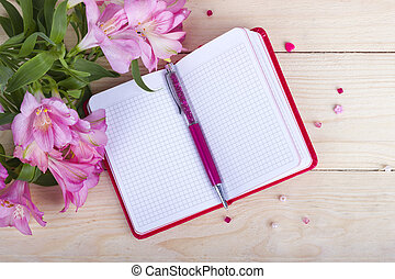 Notebook with flowers on wooden background