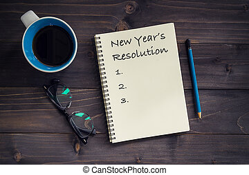 Notebook with New's Year Resolutions massage, pencil, glasses and cup of coffee on wood background.
