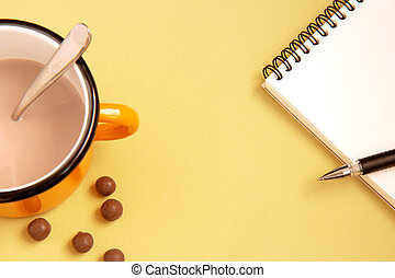 Notebook with pen and cup of cocoa on bright background