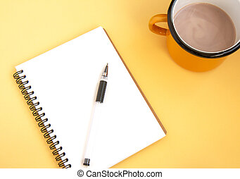 Notebook with pen and cup with cocoa on an orange background