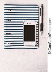 Notebook with pen and telephone on the white table vertical