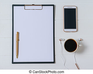 Notebook with pen, coffee, smartphone and headphones on a dark wooden table. The view from the top.