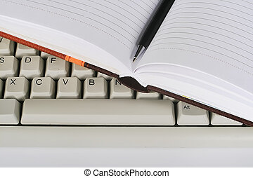 notebook with pen on keyboard