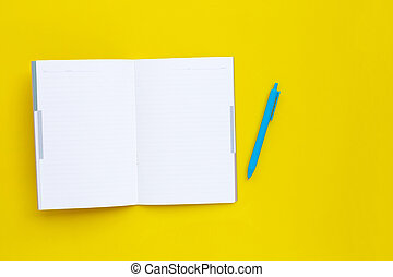 Notebook with pen on yellow background.