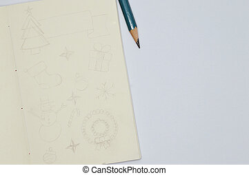 notebook with pencil sketches of christmas items on white background