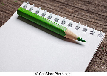 notebook with pensil on wooden background