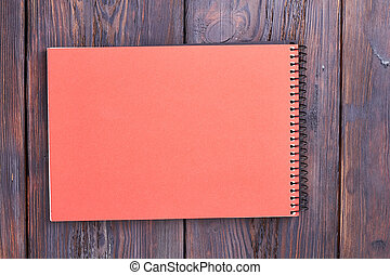 Notebook with spiral on wood.