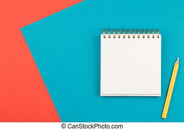 notebook with yellow pencil on twocolor background