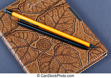 notebooks in leather covers and a pencil close up