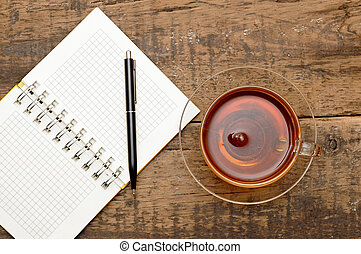 notebooks, pens, tea on the table