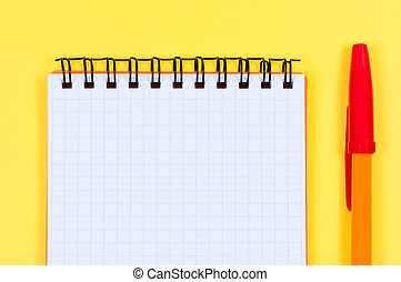 Notepad and ballpen on yellow background.