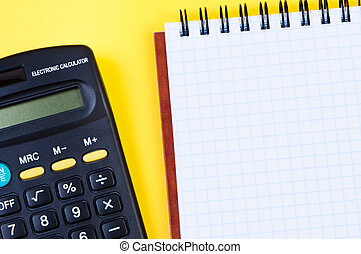 Notepad and calculator on yellow background.