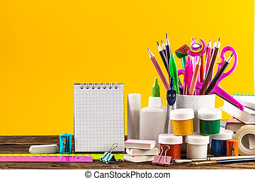 Notepad and colorful School stationery on yellow background