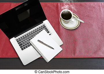 Notepad and notebook laptop on Red leather tablecloth