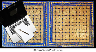 Notepad and notebook laptop on Two moroccan mosaic table