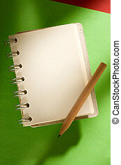 Notepad and pencil isolated on the green background
