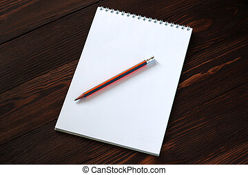 notepad and pencil on wooden background