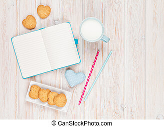 Notepad, cup of milk, heart shaped cookies and gift toy