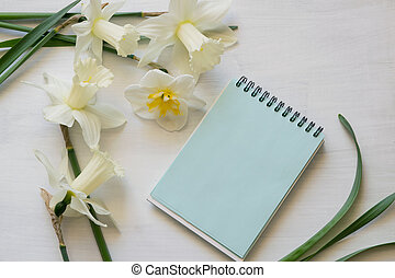 Notepad, daffodils on a white background. Inspirational workplace.