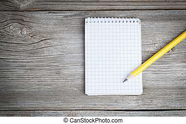 Notepad on a wooden table with pencil