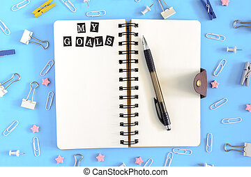 Notepad on springs with the inscription My Goals. Pages of white paper. Stationery in disorder on a blue background. View from the top.