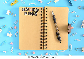 Notepad on springs with the inscription To Do List. Pages of brown paper. Stationery in disorder on a blue background. View from the top.