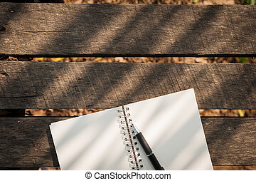 Notepad on wood table - Opened notebook with blank area for...