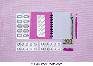 Notepad, pills and money on a pink background