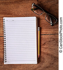 Notepad with a spiral binding on wood table