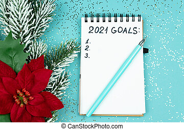 Notepad with handwrittrn 2021 goals for new year. Resolutions list.