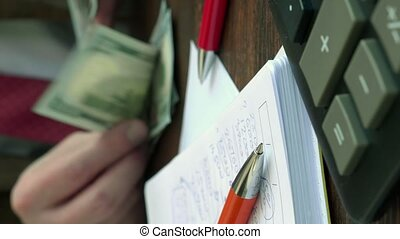 Notepad with home financial calculations and hands counts money. Vertical video.