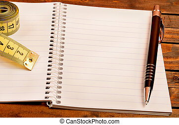 Notepad with pen and centimeter on table