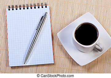 Notepad with pen and cup coffee.