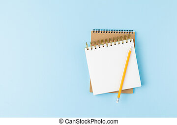 Notepad with pencil on blue background.