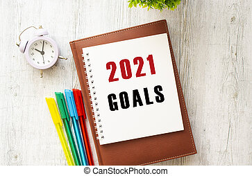 Notepad with the text 2021 GOALS on a wooden table. Brown diary and pens.