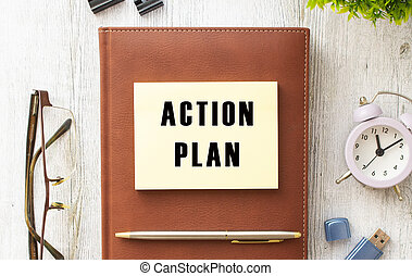 Notepad with the text ACTION PLAN on a wooden table. Brown diary and pen.