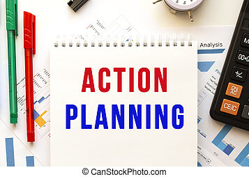 Notepad with the text ACTION PLANNING on a color financial chart. Business concept.