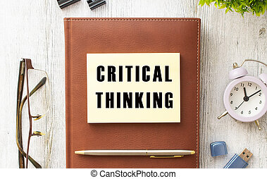 Notepad with the text CRITICAL THINKING on a wooden table. Brown diary and pen.