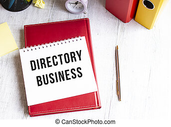 Notepad with the text DIRECTORY BUSINESS on a wooden table. Red diary and pen.