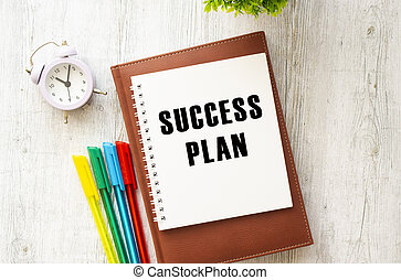 Notepad with the text SUCCESS PLAN on a wooden table. Brown diary and pens.