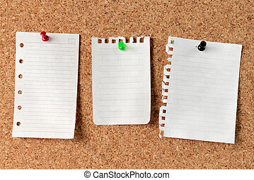 Notes on Cork Board. white note paper attached with...