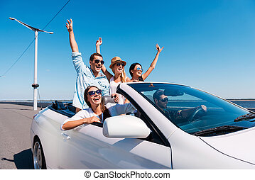 Nothing but friends and road ahead. Group of young happy people enjoying road trip in their white convertible and raising their arms up