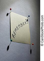 """yellow noticesheet with four pins and the word """"remember"""" written on it - gelber Notizzettel mit vier Stecknadeln, beschrieben mit dem Wort """"remember"""""""