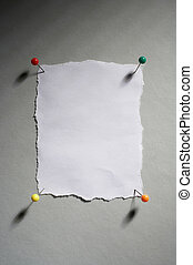 unbeschriebener weisser Notizzettel mit vier Stecknadeln- empty white memo with four pins