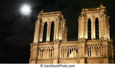 Notre Dame Cathedral, behind night sky and moon clouds